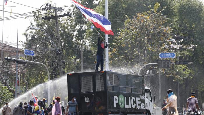 epa03973716 Thai anti-government protesters commander a police truck and taunt police at Government House as street battles for control of the seat of government continue in Bangkok, Thailand, 02 December 2013. Thousands of protesters vowed to take control of government ministries and offices including the seat of Government House in an effort to oust the government of Prime Minister Yingluck Shinawatra and its defacto leader from afar her brother Thaksin Shinawatra. EPA/BARBARA WALTON