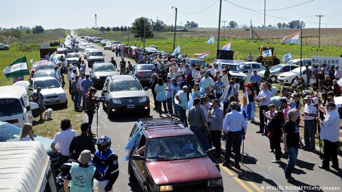 Argentinian environmentalists of the city of Gualeguaychu prepare for a protest in Arroyo Verde, Enter Rios province, Argentina, 32 km from the border with Uruguay, on October 6, 2013, against the increase of the production of Finnish pulp mill UPM, placed on the Uruguayan bank of the bordering Uruguay river. The environmentalists drove along in a convoy towards the border with Uruguay crossing the General San Martin bridge which links the countries. Members of the People's Assembly of Gualeguaychu had blocked the bridge for almost four years since November 2006, as they protested against the construction of the pulp mill. AFP PHOTO/ Miguel ROJO (Photo credit should read MIGUEL ROJO/AFP/Getty Images)