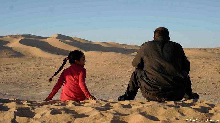 A man and a young girl sit on a sand dune in the desert (c) DW/Valerie Stocker