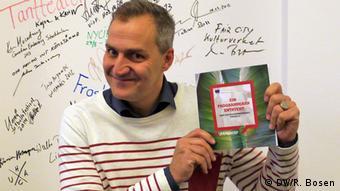 Lindegren hält ein Broschüre des Kulturprogramms hoch (Foto: Ralf Bosen/DW)
