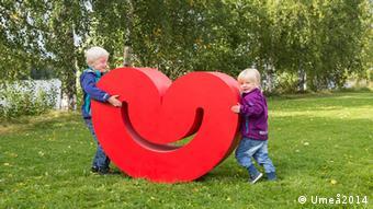 Zwei Kinder stehen lachend neben einem großem rotem Herz