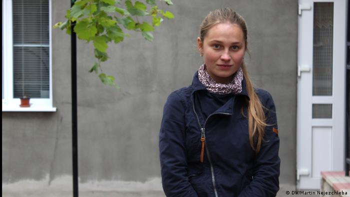 Oksana Hemei stands in front of her house