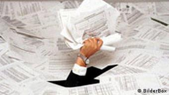 A hand holding papers sticks out of a sea of bureaucratic forms