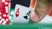 Poker player lifting the corners of two cards (Fotolia: #55679469); © Fotolia/apops