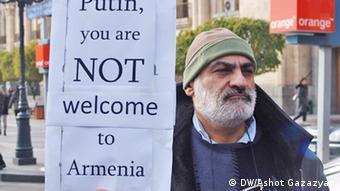 Участник акции протеста в Ереване держит плакат с надписью на английском языке: Путин не добро пожаловать в Армению