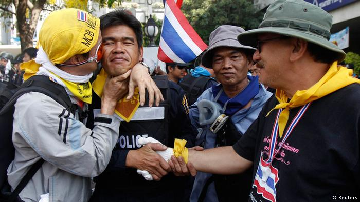 An anti-government protester kisses a riot police officer on the cheek during a rally outside the Government House in Bangkok December 3, 2013. Thai police said on Tuesday they would not stand in the way of protesters battling to seize the prime minister's office and city police headquarters, focal points of demonstrations aimed at toppling the government of Prime Minister Yingluck Shinawatra. REUTERS/Chaiwat Subprasom (THAILAND - Tags: POLITICS CIVIL UNREST TPX IMAGES OF THE DAY)