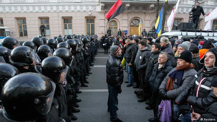 Police stand guard in front of protesters during a demonstration in support of EU integration in front of the Parliament building in Kiev December 3, 2013. Ukrainian protesters blockaded the main government building on Monday, seeking to force President Viktor Yanukovich from office with a general strike after hundreds of thousands demonstrated against his decision to abandon an EU integration pact. REUTERS/Gleb Garanich (UKRAINE - Tags: POLITICS CIVIL UNREST)