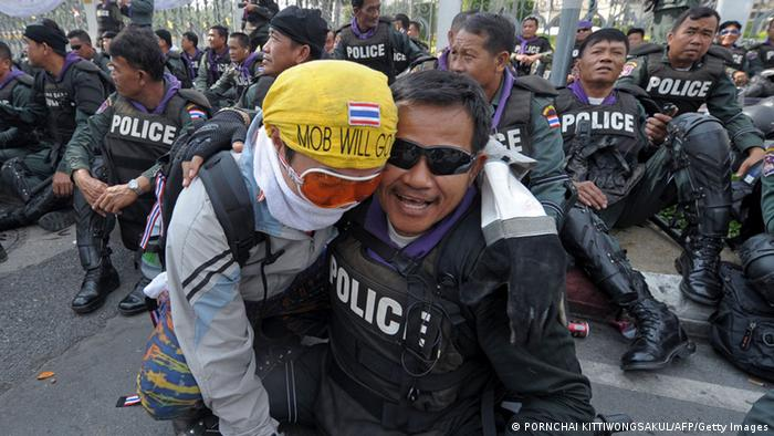 Thai riot policeman is hugged by an anti-government protester at Government House in Bangkok on December 3, 2013. Hundreds of Thai opposition protesters entered the government headquarters unopposed on December 3, after police said they would offer no resistance to the demonstrators who have vowed to topple Prime Minister Yingluck Shinawatra. AFP PHOTO / PORNCHAI KITTIWONGSAKUL (Photo credit should read PORNCHAI KITTIWONGSAKUL/AFP/Getty Images)