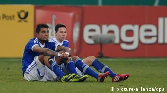 Kevin-Prince Boateng (l.) and Julian Draxler sit, disappointed, after Schalke's surprise German Cup exit at the hands of Hoffenheim, 03.12.2013. (Photo via Revierfoto)