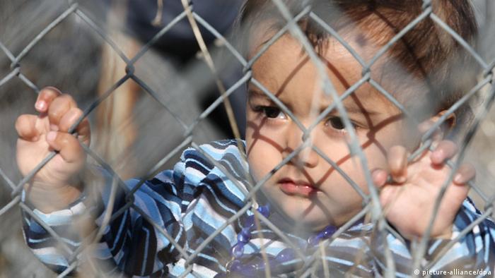 In einem Internierungslager an der türkisch griechischen Grenze Evros steht ein kleiner Junge am Zaun und blickt durch den Maschendraht. (Foto: picture-alliance/dpa)