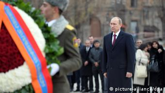 Vladimir Putin stands at a memorial for victims of the Spitak earthquake