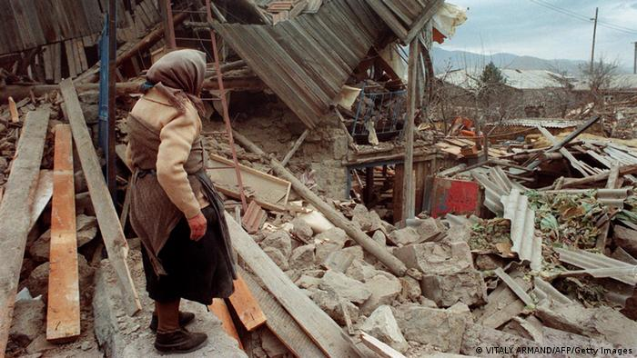 A woman looks at destroyed buildings in the aftermath of the Spitak earthquake in 1988.