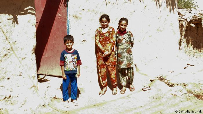 Three children outside a house