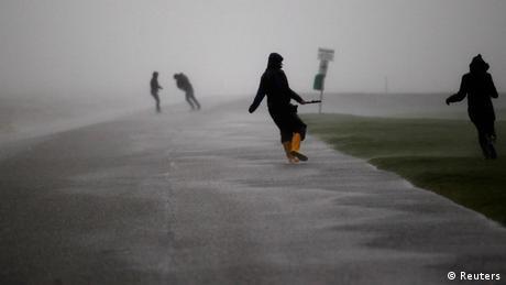 Menschen kämpfen gegen den starken Wind des Orkantiefs Xaver an.