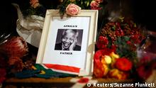 Flowers and tributes are left on the Nelson Mandela statue on Parliament Square in London December 6, 2013. South African anti-apartheid hero Mandela died peacefully at home at the age of 95 on Thursday after months fighting a lung infection, plunging his nation and the world into mourning for a man revered as a moral giant. REUTERS/Suzanne Plunkett (BRITAIN - Tags: SOCIETY POLITICS OBITUARY)
