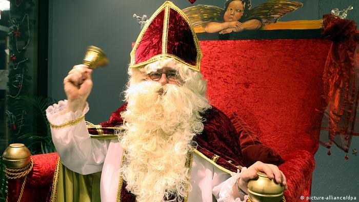 Ein als Nikolaus verkleideter Mann läutet mit einer Glocke