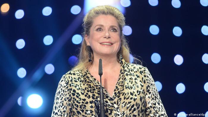 Catherine Deneuve stands a microphone onstage with lights shining behind her