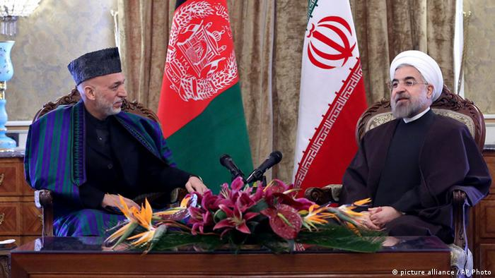 Iran's President Hassan Rouhani, right, speaks with Afghan President Hamid Karzai, during their meeting at Tehran's Saadabad Palace in Iran, Sunday, Dec. 8, 2013. (AP Photo/Ebrahim Noroozi)