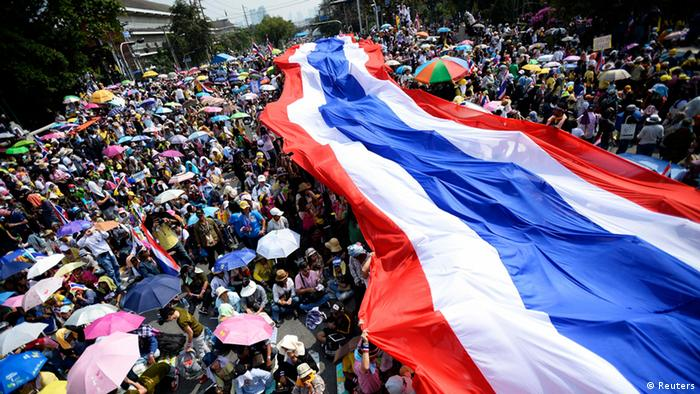Bangkok Proteste 09.12.2013 - Anti-government protesters unveil a large Thai flag as they descend on Government House in Bangkok December 9, 2013. (Photo: Reuters)