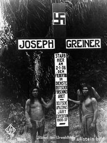Indigenous people stand in front of a big cross with a swastika at the burial site of Joseph Greiner
