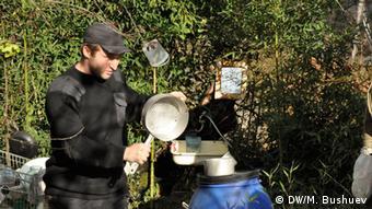 Ilya Samesin standing outside, holding a pot (c) DW/M. Bushuev