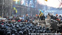 Riot policemen stand in front of a barricade held by protesters on Independence Square in Kiev, on December 11, 2013. Ukrainian security forces on Wednesday stormed Kiev's Independence Square which protesters have occupied for over a week but the demonstrators defiantly refused to leave and resisted the police in a tense standoff. Eite Berkut anti-riot police and interior ministry special forces moved against the protestors at around 2:00 am (midnight GMT) in a move that prompted US Secretary of State John Kerry to express disgust over the crackdown. AFP PHOTO/ GENYA SAVILOV (Photo credit should read GENYA SAVILOV/AFP/Getty Images)