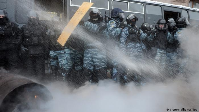 Opponents of the Ukranian government protest against the decision to not sign an EU association agreement and splash ice-cold water onto police forces moving in