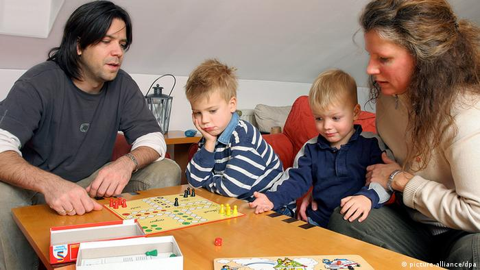 Eine Familie mit zwei Kindern spielt ein Brettspiel (Foto: Heiko Wolfraum, dpa)