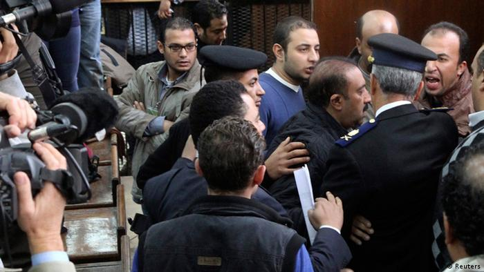 Defendants quarelling with police at Wednesday's trial.