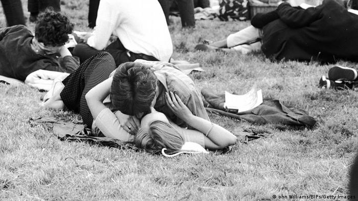 black and white photo of young couple lying on grass kissing at festival (ohn Williams/BIPs/Getty Images)
