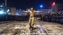 A ^protester stands next to riot policemen getting ready to launch an assault to a barricade held by protesters on Independence Square in Kiev late on December 11, 2013. Ukrainian security forces on Wednesday stormed Kiev's Independence Square which protesters have occupied for over a week but the demonstrators defiantly refused to leave and resisted the police in a tense standoff. Eite Berkut anti-riot police and interior ministry special forces moved against the protestors at around 2:00 am (midnight GMT) in a move that prompted US Secretary of State John Kerry to express 'disgust' over the crackdown. AFP PHOTO/ DMITRY SEREBRYAKOV (Photo credit should read DMITRY SEREBRYAKOV/AFP/Getty Images)
