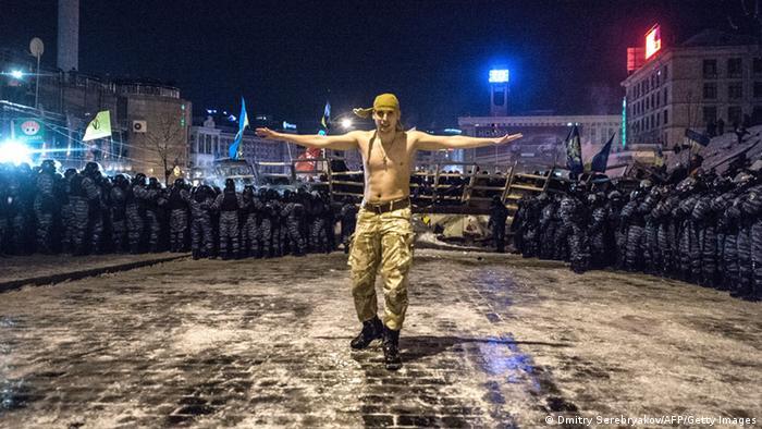 Протестующий на Майдане в декабре 2013 года на фоне бойцов украинского спецназа