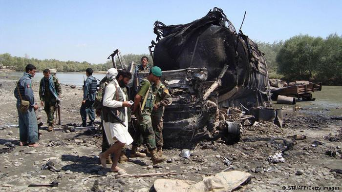 Members of the security forces walk at the site of a NATO airstrike which destroyed two fuel tankers hijacked by the Taliban in northern Kunduz