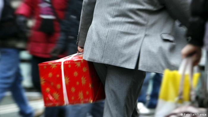Stressful images of a man carrying a Christmas package (Fotolia/Alliance)