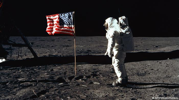 Astronaut Edwin Buzz Aldrin stands on the surface of the moon with the American flag next to him. 