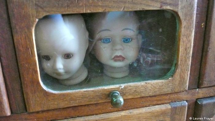Two doll heads in a glass case