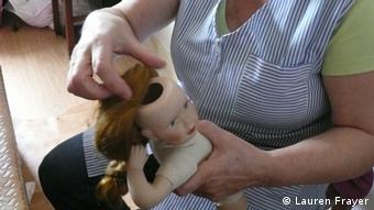 A doctor wearing an apron performs a hair transplant on a doll
