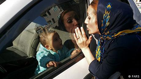 صورة رمزية من إيران لطفل داخل سيارة مغلقة وسيدة تتواصل معه عبر النافذة المغلقة