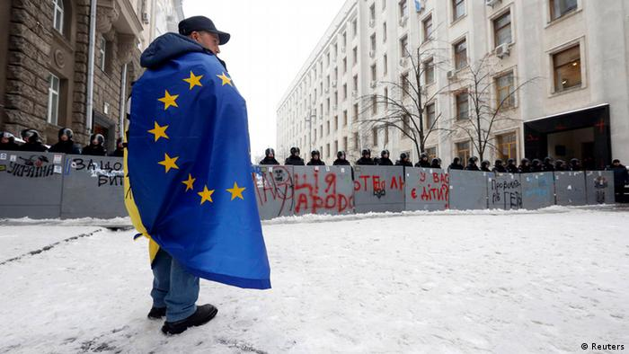 A man wrapped in a European flag stands in front of police barricades in Kyiv. (Photo: REUTERS/Alexander Demianchuk)