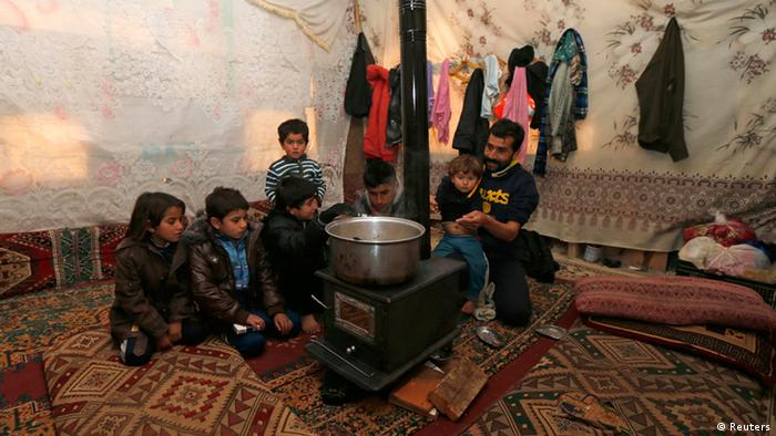 A family of seven sits around a pan on a stove in a tent (Foto: Mohamed Azakir/REUTERS)