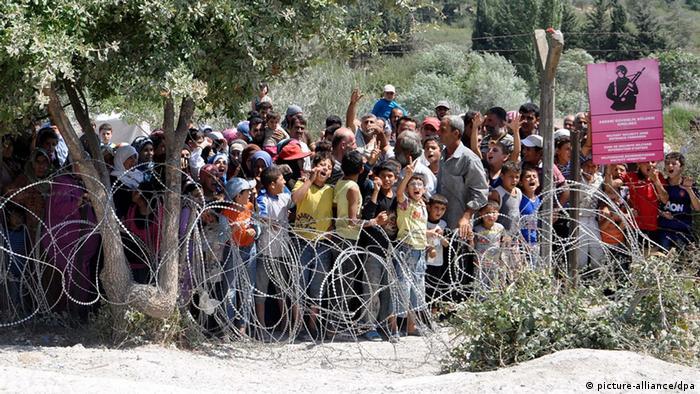 Syrische Flüchtlinge stehen an der mit Stacheldraht gesicherten Grenze zur Türkei und warten auf den Transport in ein Flüchtlings-Camp. (Foto: picture-alliance/dpa)