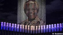Candles are lit under a portrait of former South African President Nelson Mandela before his funeral ceremony in Qunu December 15, 2013. REUTERS/Odd Andersen/Pool (SOUTH AFRICA - Tags: OBITUARY POLITICS)