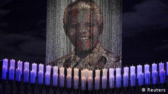 Candles under a portrait of Nelson Mandela