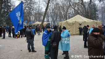 People with blue flags stand in a park (Foto: Roman Goncharenko/DW)