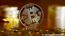ILLUSTRATION - Bitcoin-Münzen, fotografiert am 28.11.2013 in Berlin beim Münzhandel BitcoinCommodities. Bitcoin ist eine Form von virtuellem Geld, das in einem Computernetz verwaltet wird. Münzen tragen unter einer Folie mit einem Hologramm einen privat key, eine Zahlenfolge, die mit einem Bitcoin-Wert versehen ist. Importiert man den Code in eine Software Wallet, kann man den Wert elektronisch ausgeben, einkaufen oder an Online-Börsen gegen andere Währungen eintauschen. Foto: Jens Kalaene