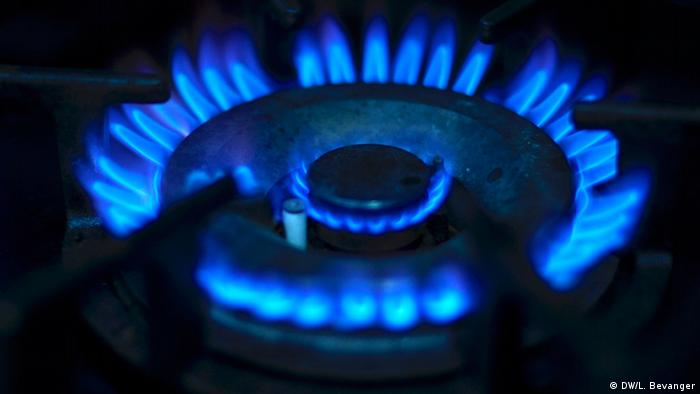 A gas ring burns with a blue flame