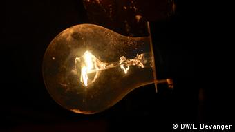 A lightbulb shines dimly in the dark