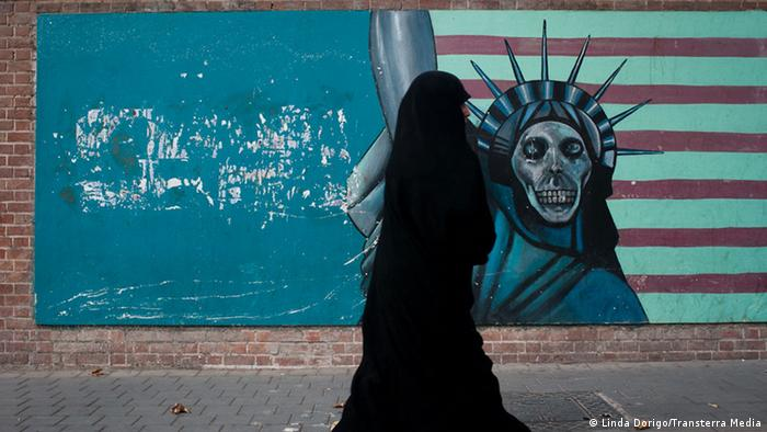 A woman in a black veil walks past a mural which shows the statue of Liberty as a skeleton.