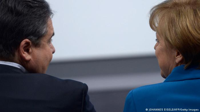 Sigmar Gabriel faces Chancellor Angela Merkel to his right. Their two parties form the majority of the country's governing Grand Coalition.