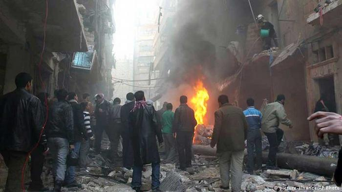 Syrians gather around damaged buildings while others try to extinguish fires following a Syrian government airstrike in Aleppo, Syria. Photo: AP Photo/Aleppo Media Center, AMC